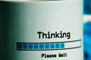 "A mug with the inscription ""Thinking ... Please Wait""."